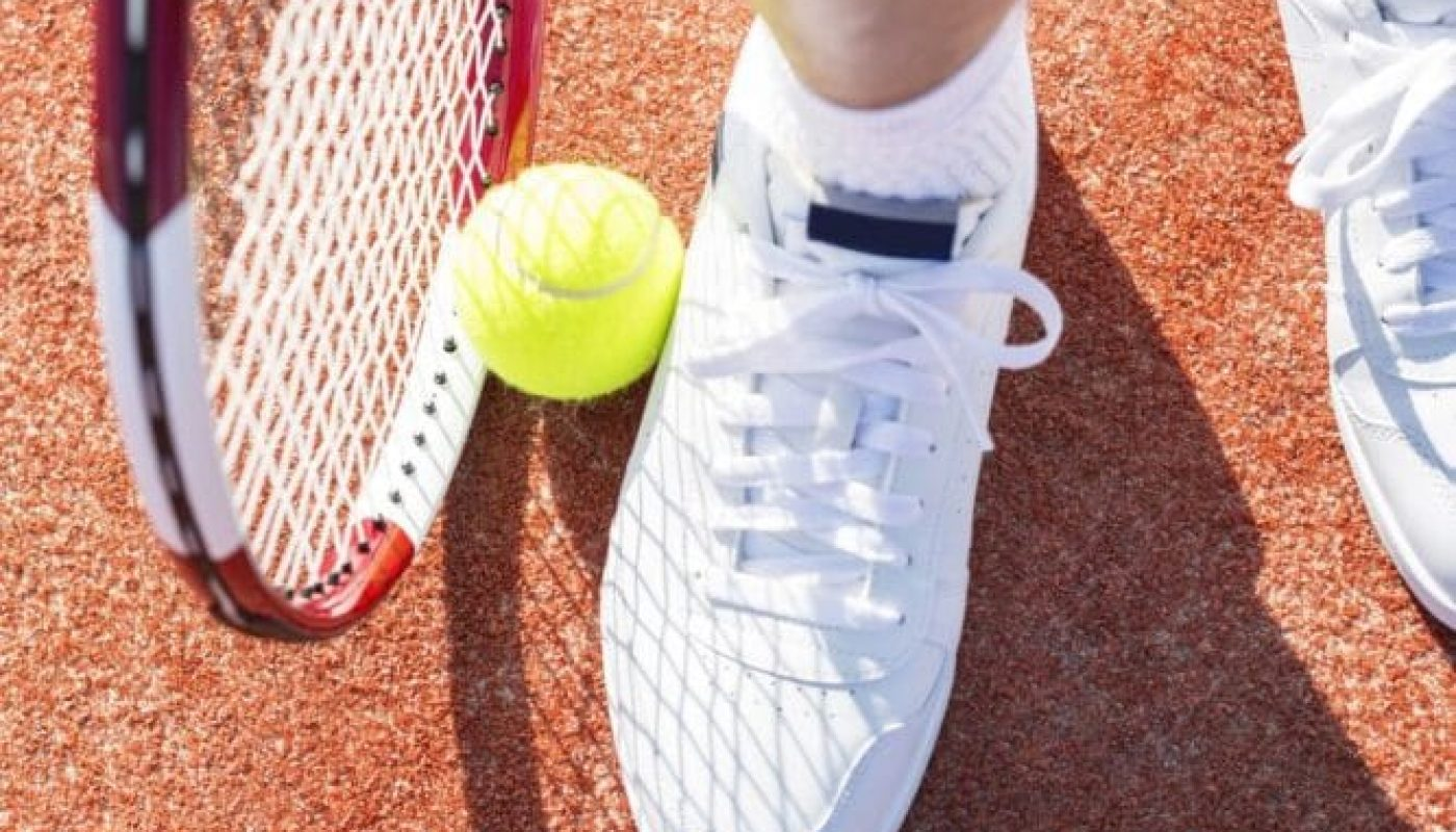 sea meadow tennis shoe, tennis ball and racket on court